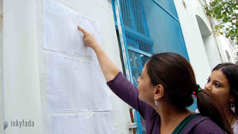 Une jeune femme cherche le rang de son nom sur la liste, pour pouvoir voter plus rapidement.